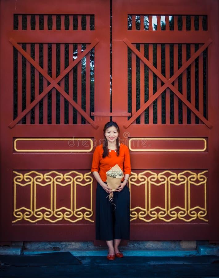 Porte en bois rouge, fille dans la robe rouge photo libre de droits