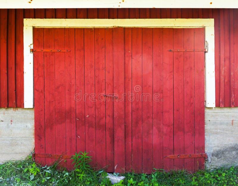 Porte en bois rouge verrouillée dans le mur rural de grange photo stock