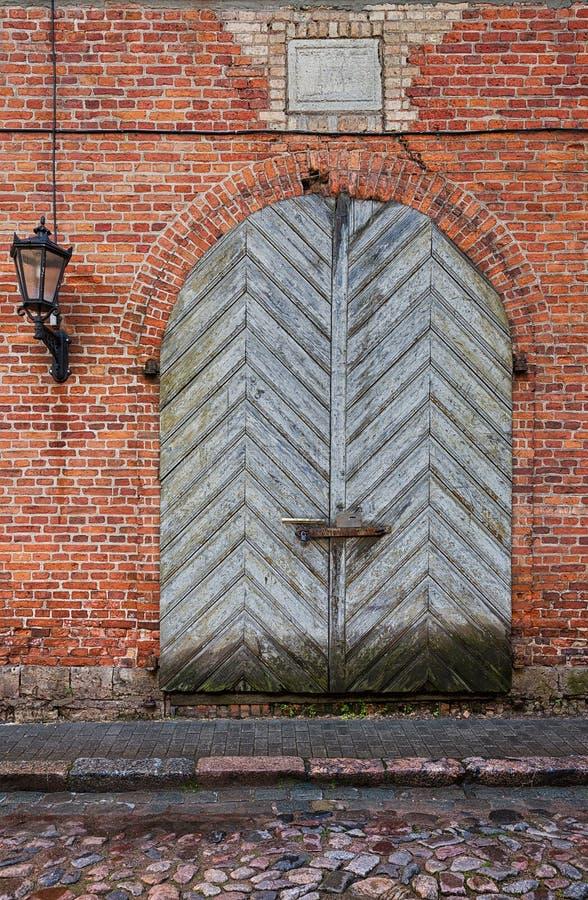 Porte en bois rustique dans le mur de briques rouge image stock
