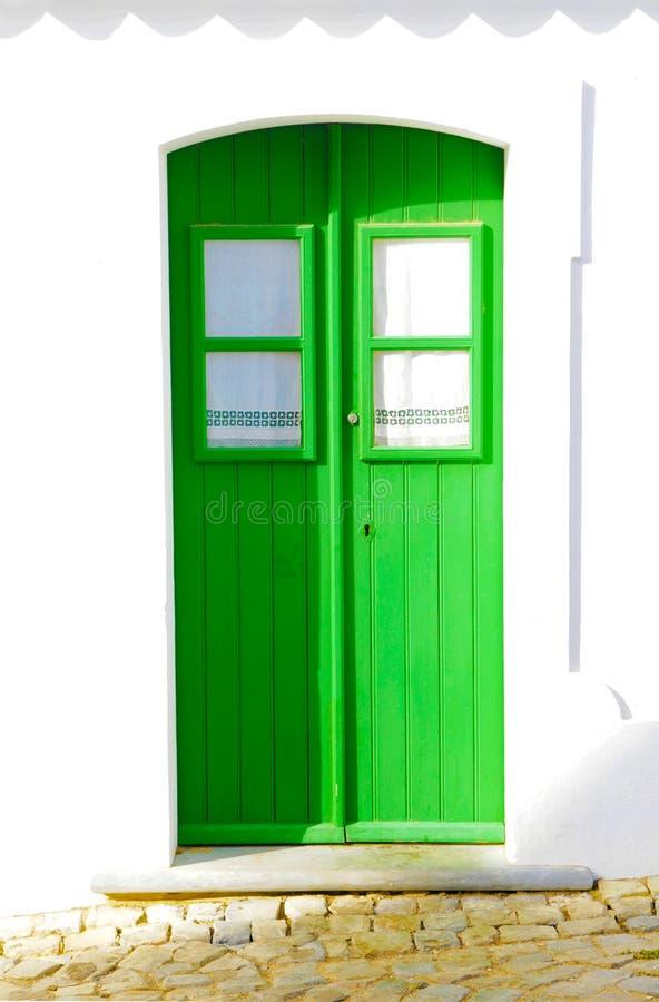 Porte en bois verte, façade à la maison blanche étrange photographie stock