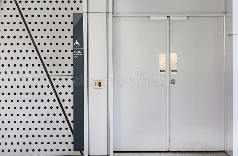 Porte en métal pour l'entrée handicapée seulement avec la poussée des textes sur la porte photos libres de droits