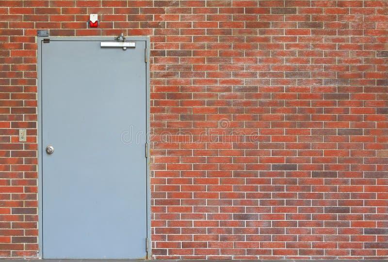 Porte en métal sur le mur de briques orange avec l'espace de copie photographie stock libre de droits