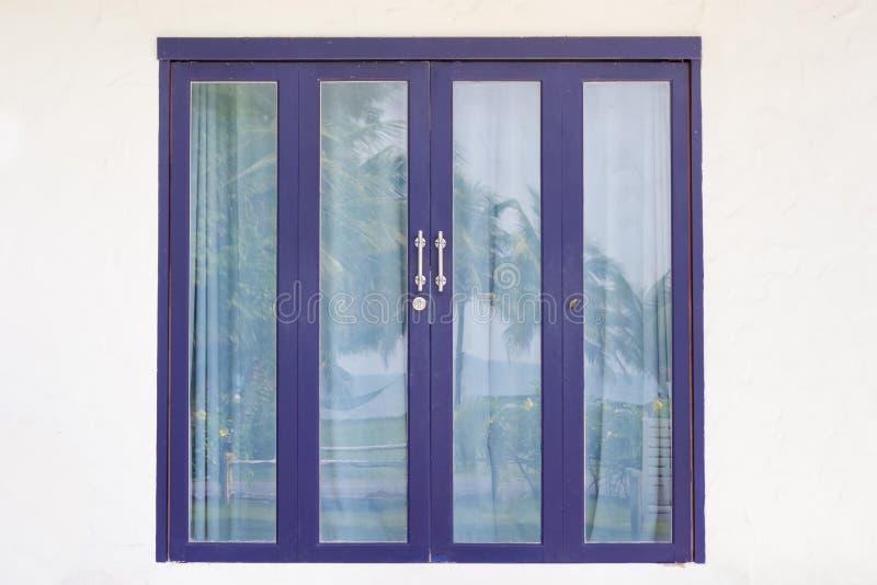 Porte en verre bleue dans un mur blanc images libres de droits