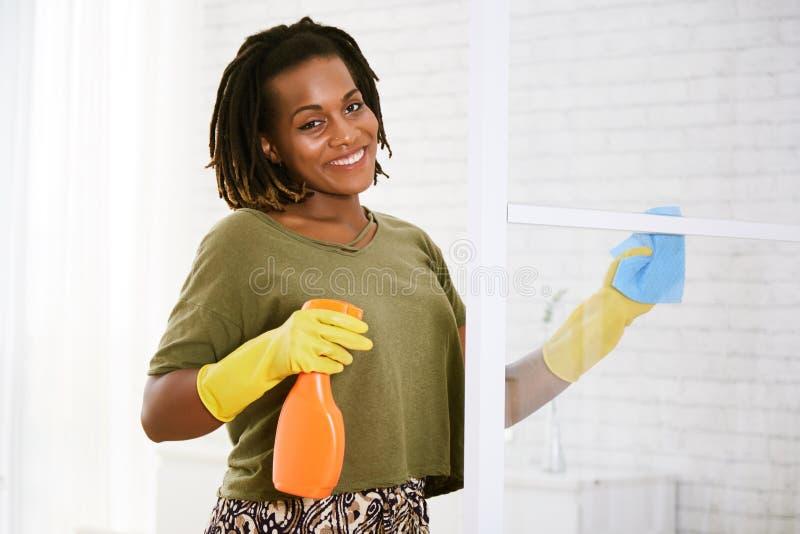 Porte en verre de nettoyage de femme images stock