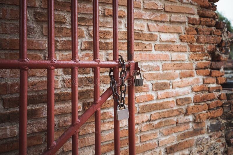 Porte et serrure et chaîne en acier de clé avec le vieux backgr rouge de mur de briques image stock