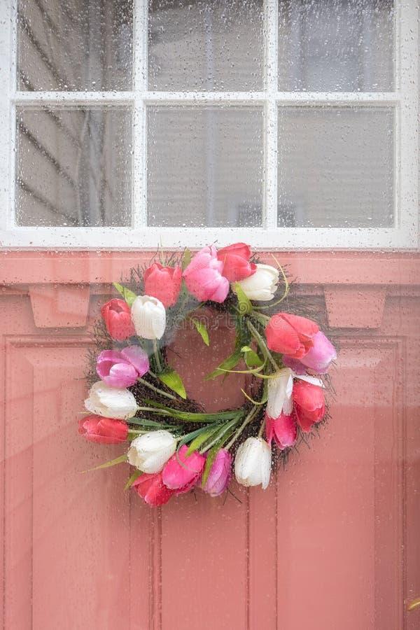 Porte extérieure rose avec la guirlande de ressort le jour pluvieux photo libre de droits