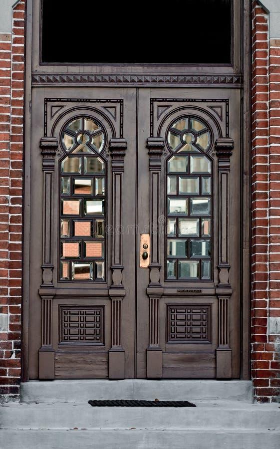 Porte fleurie dans le mur de briques photos stock