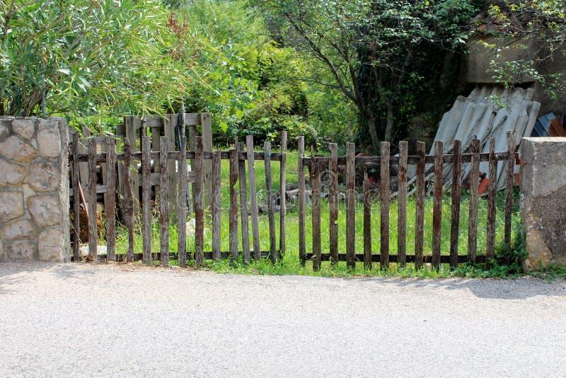 Porte improvvisate del recinto del cortile fatte dei bordi di legno stretti montati sulla parete di pietra tradizionale con il ma fotografia stock