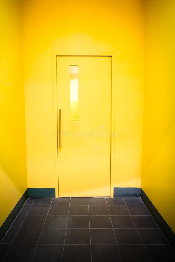 porte jaune sur le mur jaune images stock