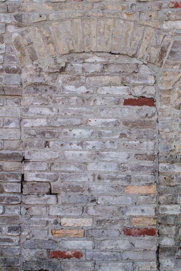 Porte murée avec les briques battues et l'arc aérien photographie stock