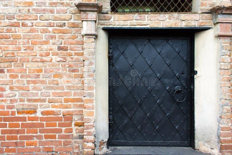 Porte noire de fer dans un mur de briques images libres de droits
