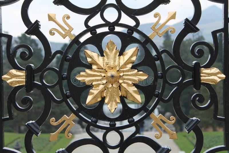 Porte noire de fer travaillé d'or d'annonce photographie stock libre de droits