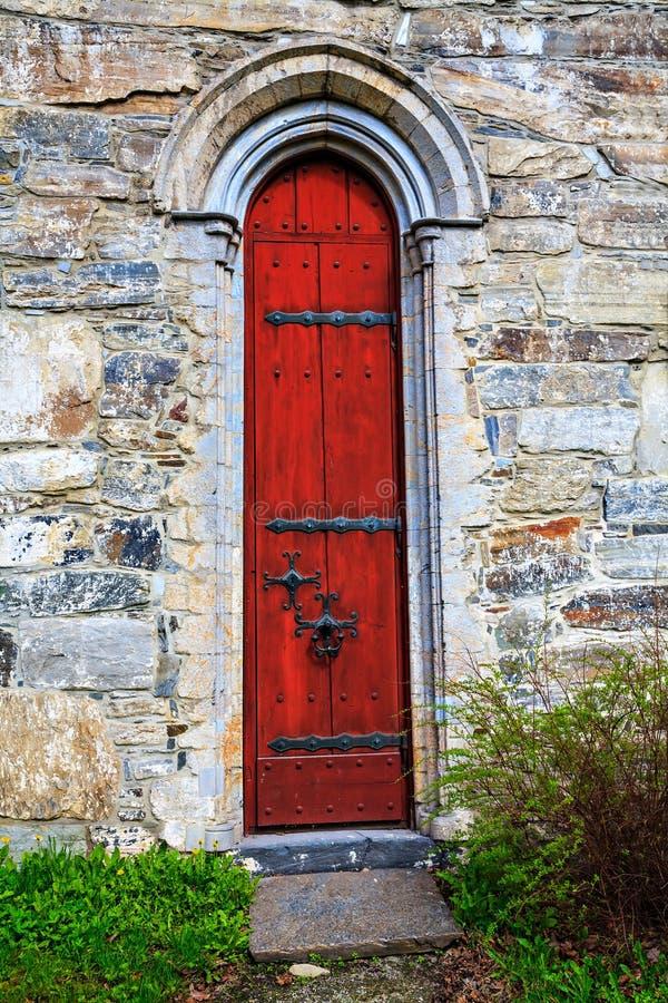 Porte rouge avec les éléments en pierre découpés dans le cadre photo libre de droits
