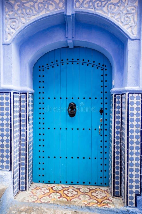 Porte traditionnelle peinte par bleu dans Chefchaouen image stock