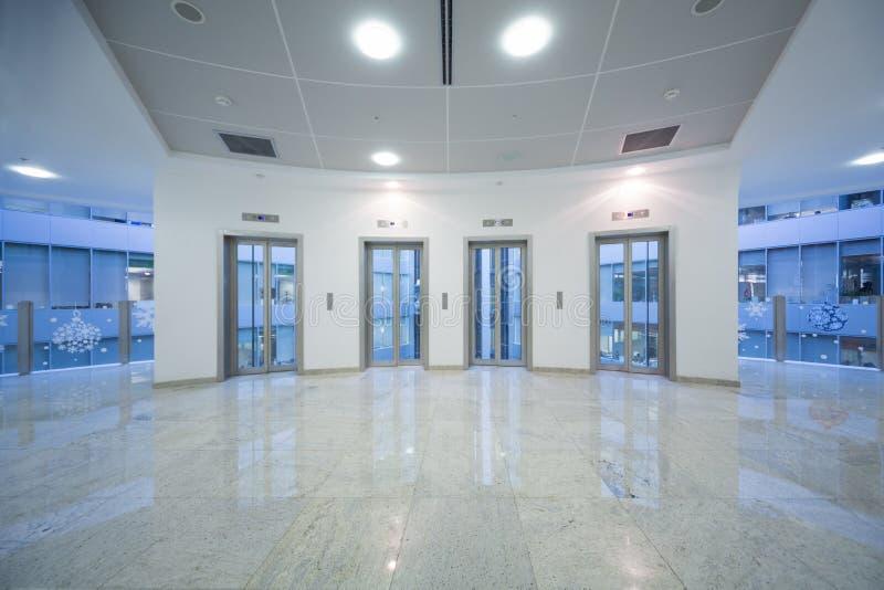 Porte transparente de l'ascenseur quatre dans le bâtiment d'affaires photographie stock libre de droits
