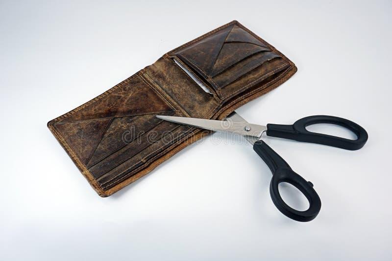 Portefeuille avec des ciseaux sur le fond de petit morceau image stock
