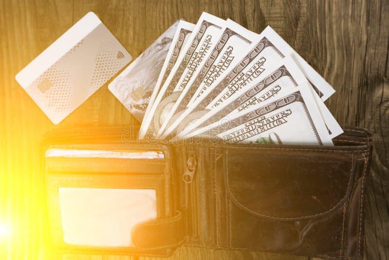 Portefeuille en cuir avec des centaines et cartes de crédit se trouvant sur une table en bois photo stock