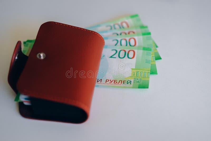 Portefeuille en cuir de Brown avec les cartes en plastique et banque des billets de banque de la Russie Argent russe pour 200 rou images stock