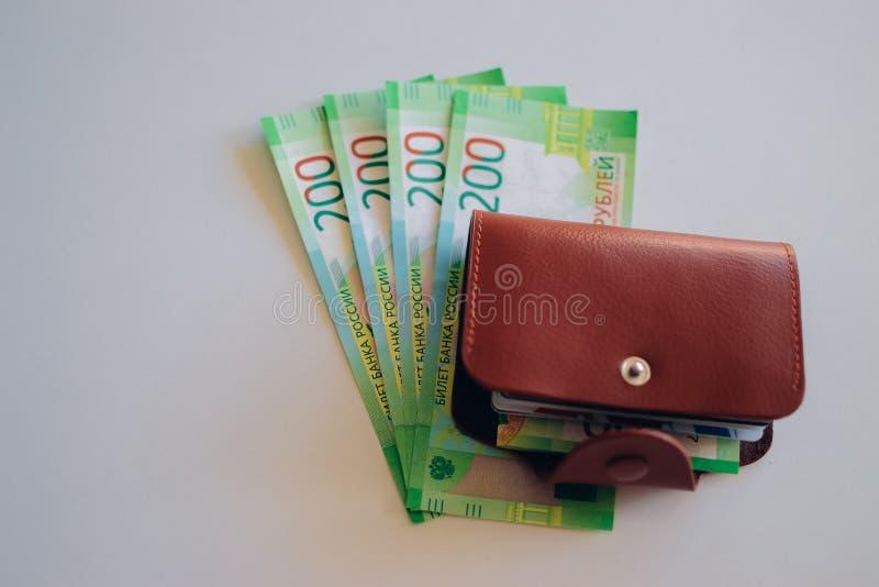 Portefeuille en cuir de Brown avec les cartes en plastique et banque des billets de banque de la Russie Argent russe pour 200 rou photographie stock