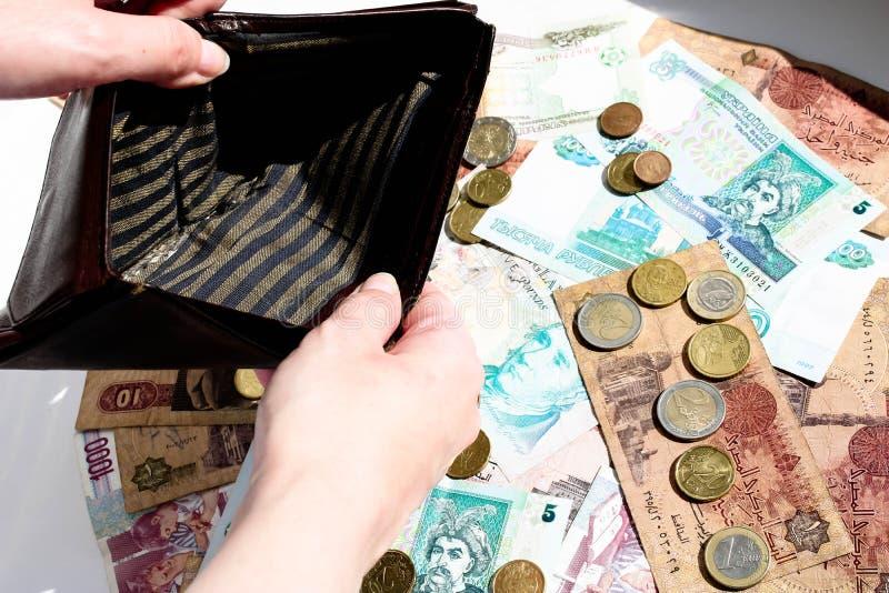 Portefeuille et point d'interrogation vides des pièces de monnaie sur le fond de billets de banque images libres de droits