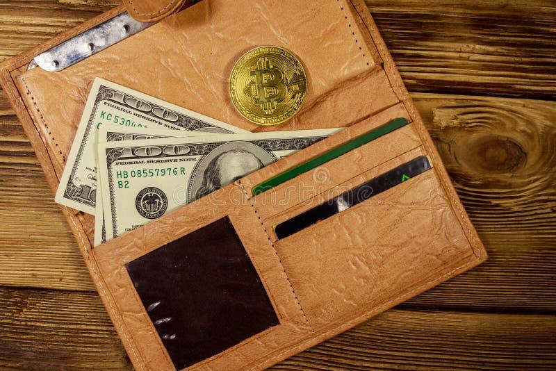 Portefeuille met Amerikaanse honderd dollarsrekeningen en gouden bitcoin op houten achtergrond stock afbeeldingen