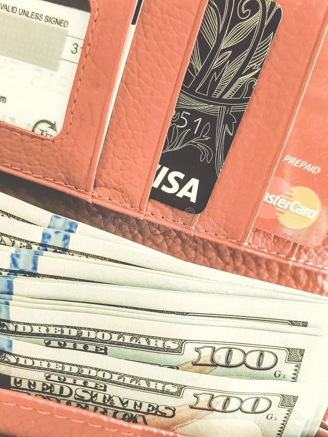 Portefeuille rouge avec des dollars et des cartes de crédit images stock