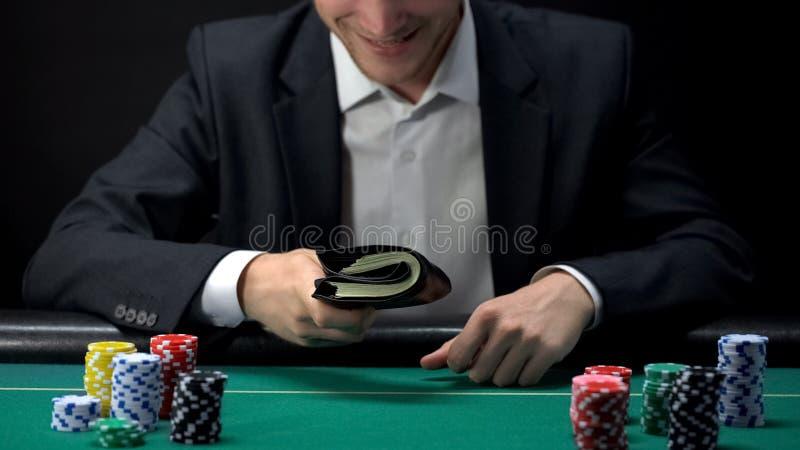 Portefeuille se tenant masculin heureux complètement d'argent, prix de gros lot, fortune de jeu, jouant photo libre de droits