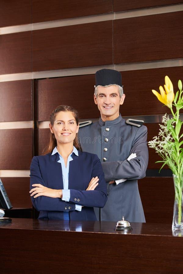 Porteiro e recepcionista na recepção do hotel foto de stock