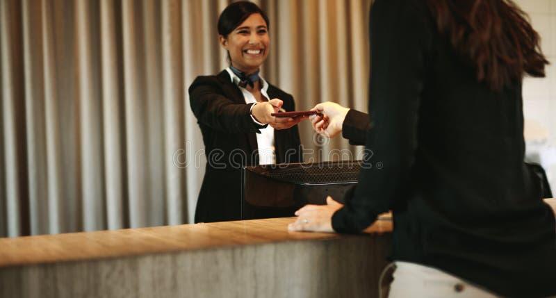 Porteiro que retorna os originais ao convidado do hotel fotos de stock