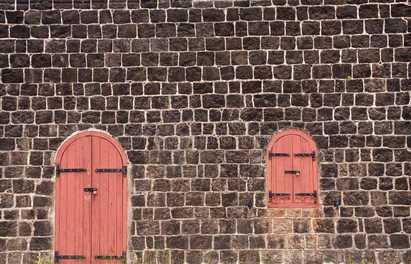 Portello e finestra rossi Locked sulla vecchia parete di pietra fotografia stock libera da diritti