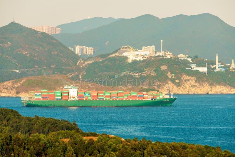 Porten av Hong Kong är en av de mest upptagna behållareportarna i världen Behållareskeppet sänder last längs den östliga Lamma ka royaltyfri foto