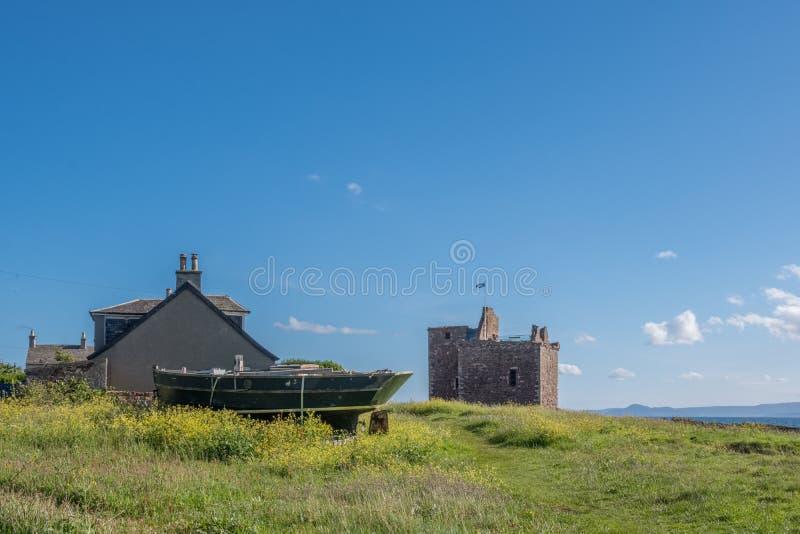 Portencross Podpalany patrzeć nad ruinami stara łódź i starymi kasztel ruinami na lata solstice w Szkocja w póżno zdjęcie royalty free