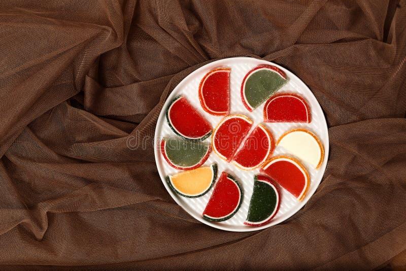 Portent des fruits les tranches colorées de confiture d'oranges sur une vue supérieure de plat blanc photos stock