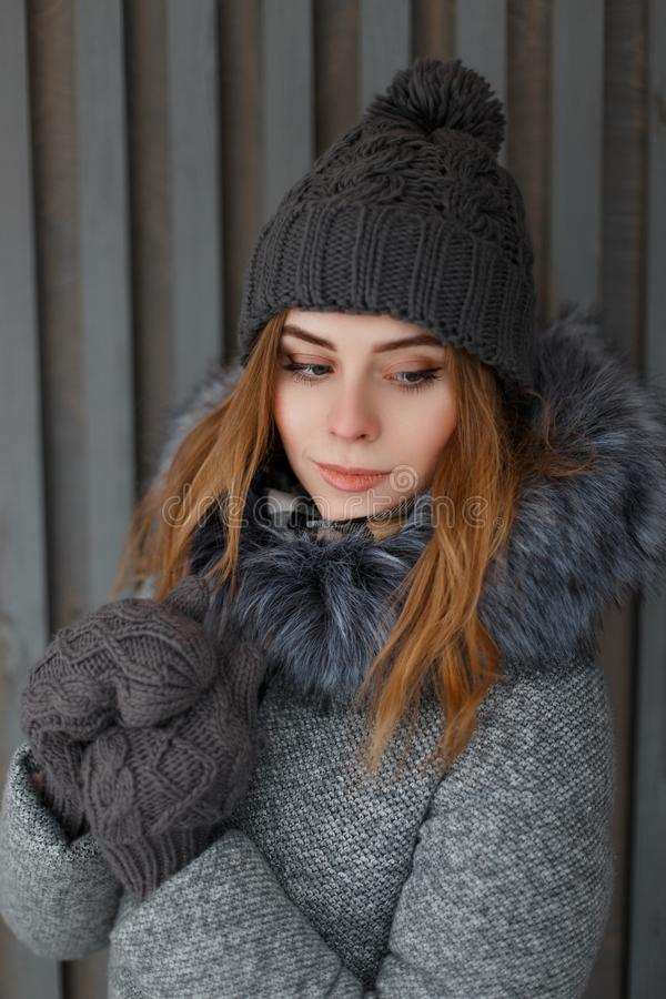 Porter of a charming cute young woman in a knitted hat in a gray winter coat with fur in vintage mittens. On the background of a wooden wall. Beautiful girl of stock photography