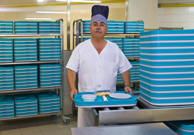 Porter With Plastic Trays In Hospital Kitchen royalty free stock photography