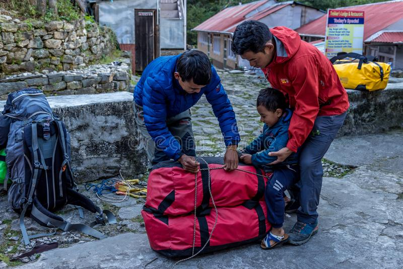 Porter tied trekking bag and one child play around in Khumbu,nepal royalty free stock photography