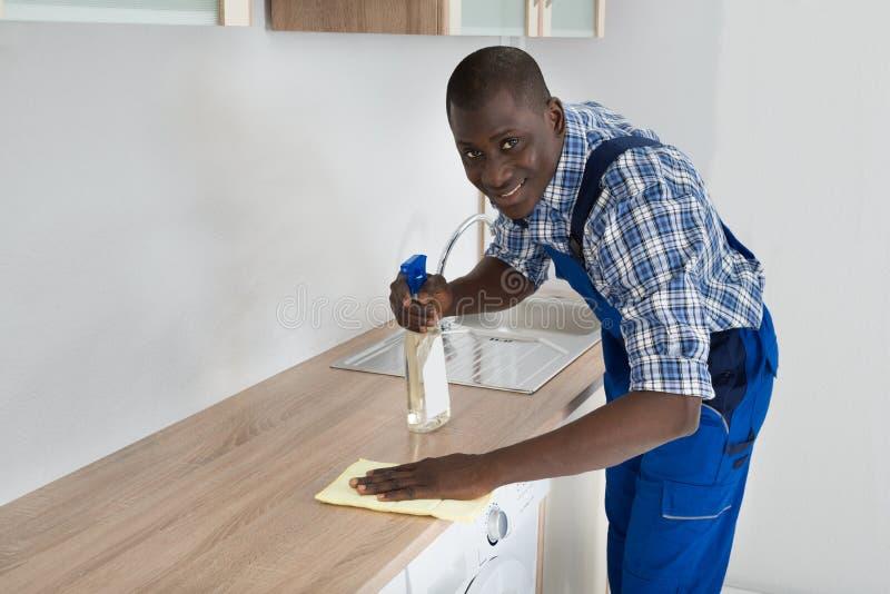 Portero Cleaning Kitchen Worktop foto de archivo
