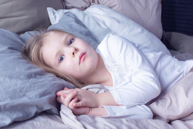 Portero de una niña con el pelo rubio El bebé está en su cama foto de archivo libre de regalías