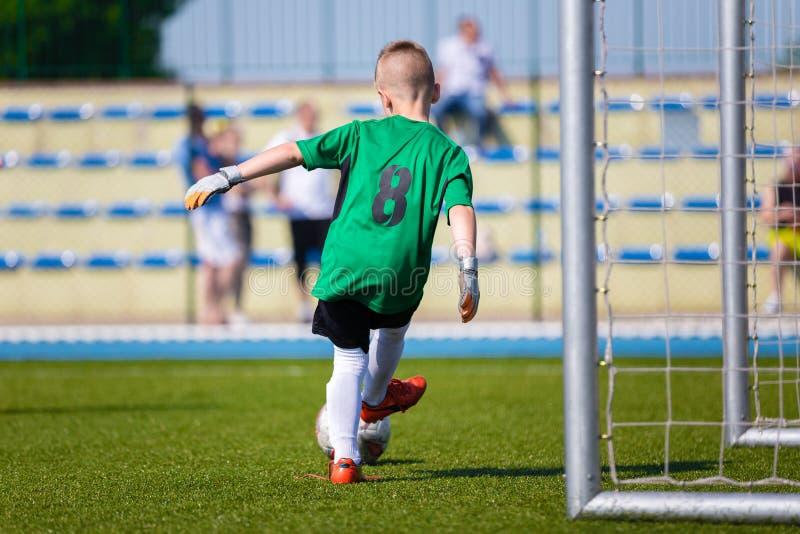 Portero joven del fútbol del fútbol del muchacho que golpea el balón de fútbol con el pie en un SP imagen de archivo