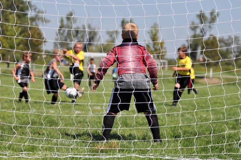 Portero joven del fútbol a través de la red fotos de archivo libres de regalías