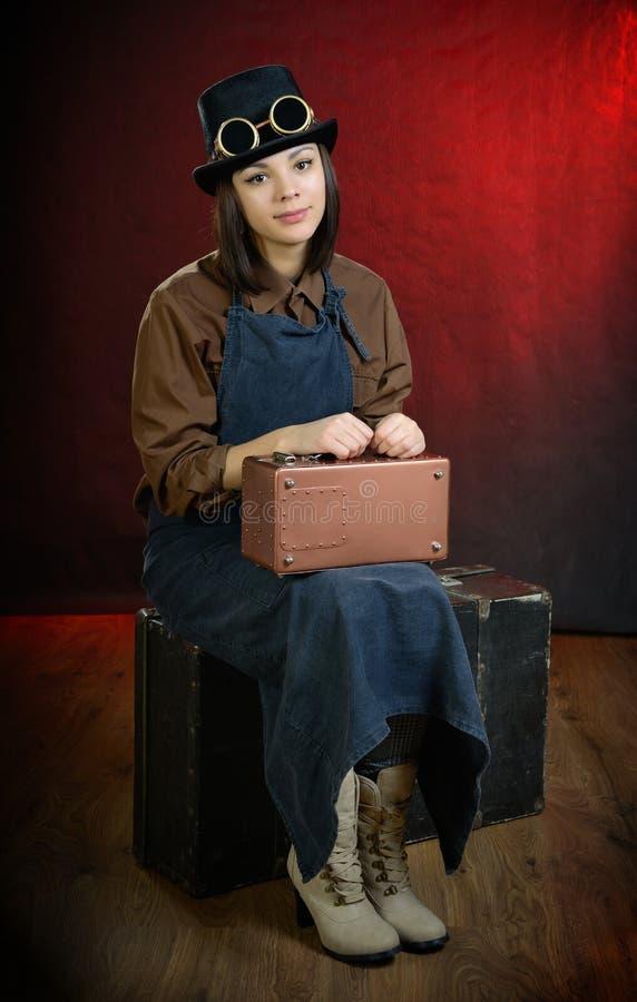 Portero punky de la muchacha del vapor que se sienta en la maleta fotografía de archivo libre de regalías