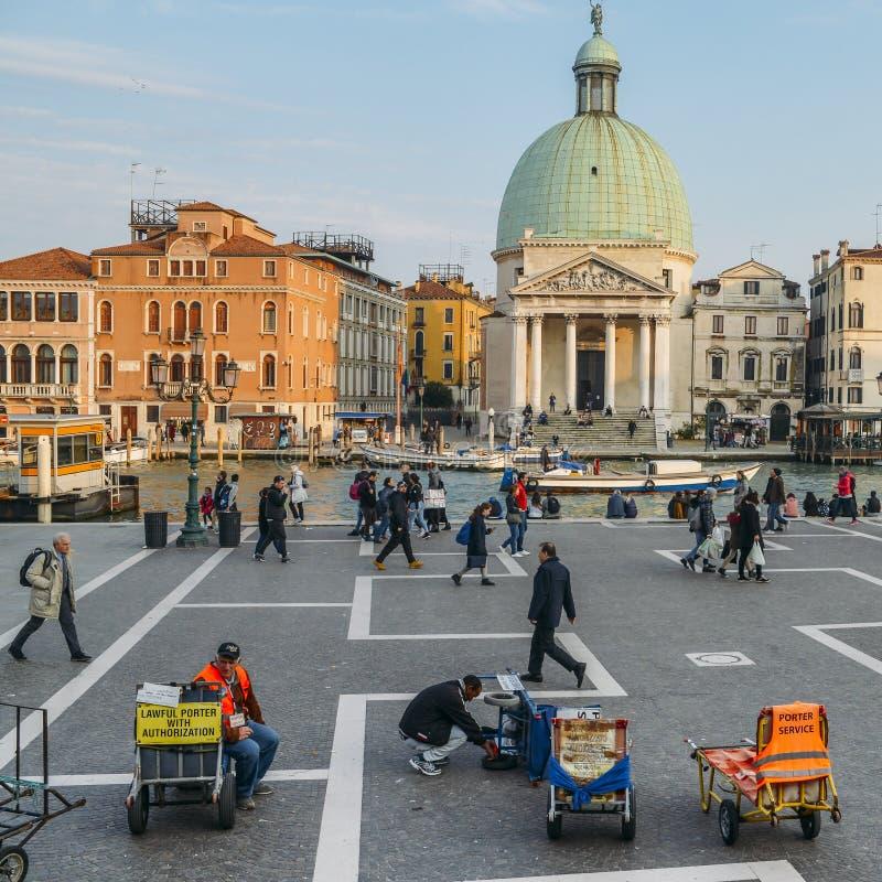 Porteros del equipaje que hacen publicidad de sus servicios delante del ferrocarril del ` s Santa Lucia de Venecia imágenes de archivo libres de regalías