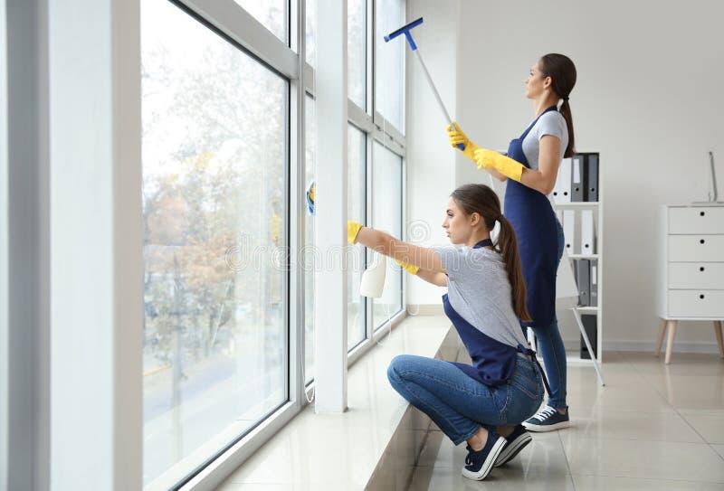 Porteros que lavan la ventana en oficina fotos de archivo libres de regalías