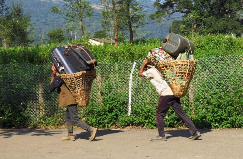 Porteros que llevan el equipaje pesado en una cesta fijada con una correa principal, Tumlingtar, Khandbari, Nepal fotos de archivo libres de regalías
