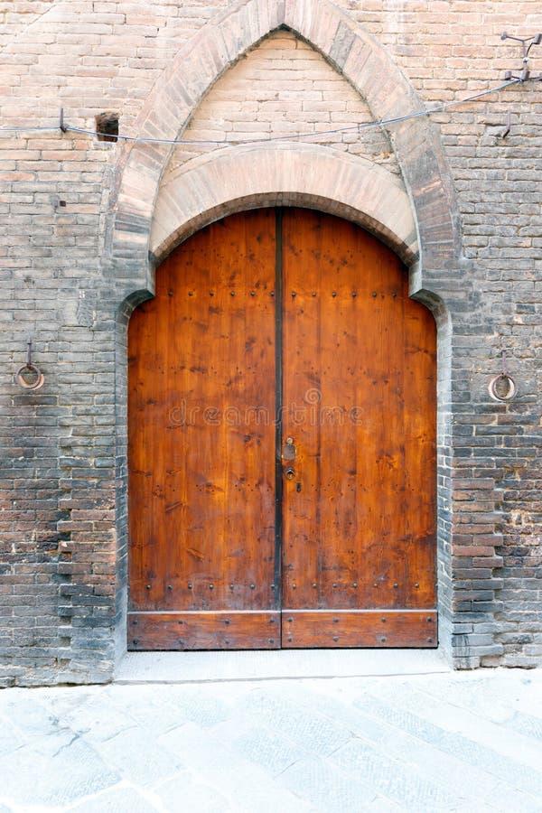 Portes à deux battants boisées antiques dans un mur de briques avec la voûte décorative images stock