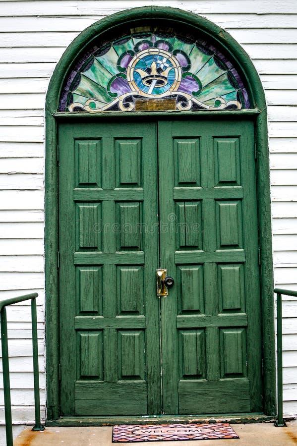 Portes d'église arquées par vert avec la couronne et la croix photo stock