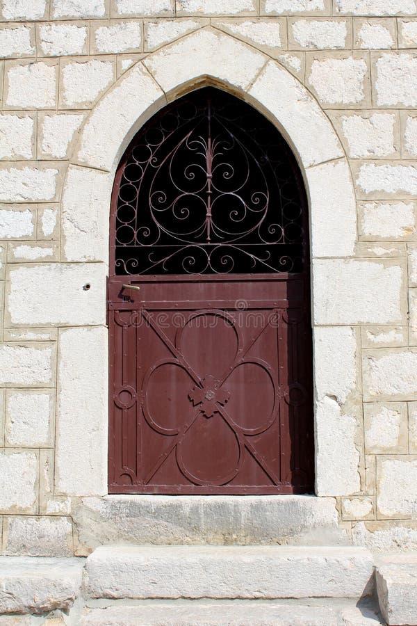 Portes d'entrée vénitiennes en métal de style avec les charnières fortes et la poignée de porte polie montées sur le mur en pierr images stock