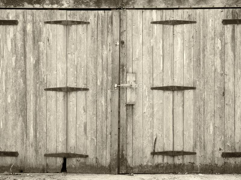 Portes en bois de planche de vieille planche grise rurale monochrome avec une attache de boulon et des charnières rouillées de fe image libre de droits