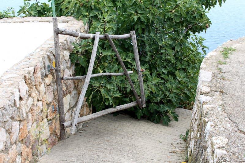 Portes en bois improvisées d'arrière-cour faites de bâtons en bois entourés avec le mur en pierre traditionnel et le chemin concr photographie stock libre de droits
