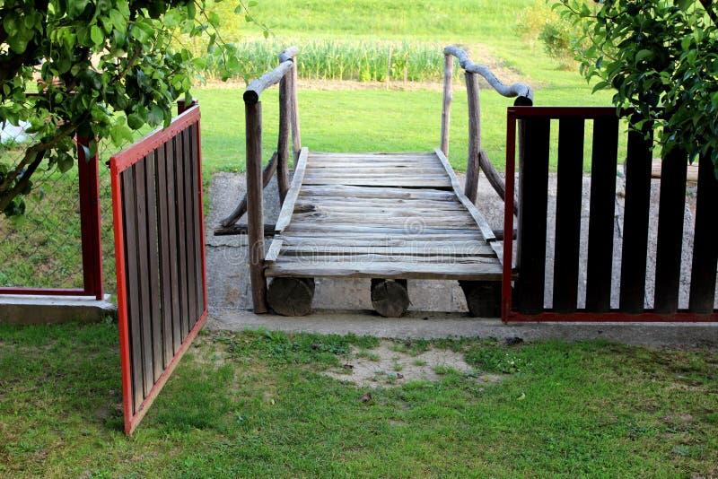 Portes en bois ouvertes de barrière d'arrière-cour menant vers de petits conseils en bois et pont de rondins au-dessus du canal é images stock